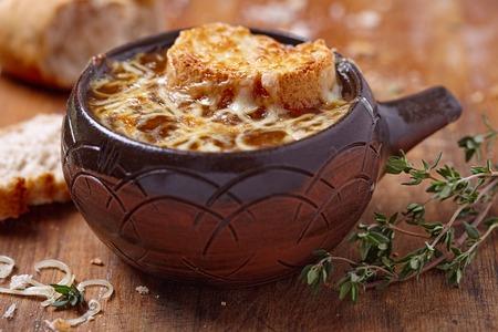 pan frances: Sopa de cebolla franc�s en la mesa de madera r�stica Foto de archivo
