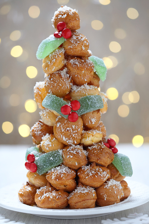 profiterole: Croquembouche with Holly Berry Decoration for Christmas Stock Photo