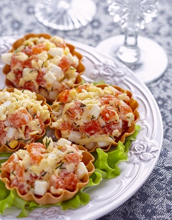 Tartlet stuffed with salmon salad with cheese and egg photo