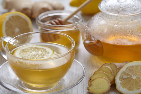 yellow tea pot: Cup of ginger tea with honey and lemon on wooden table Stock Photo