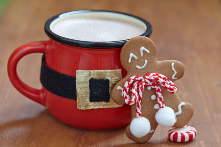 Red mugs with hot chocolate, marshmallows and gingerbread man Stock Photo