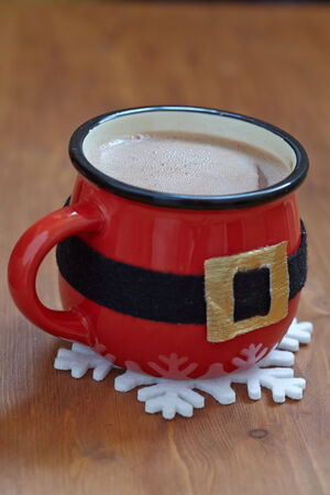 Red mugs with hot chocolate, marshmallows and gingerbread man photo