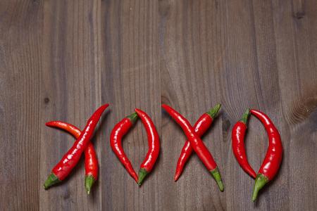xoxo: Chili pepper xoxo on a wooden background