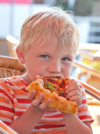 Little boy eating pizza in a restaurant photo