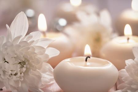 蝋燭および木製のテーブルの花