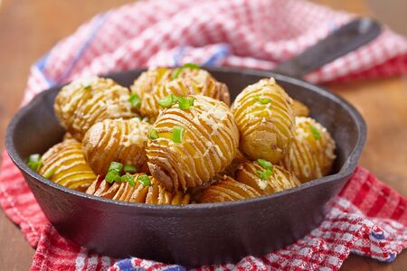 Baked hasselback potatoes with cheese and green onion