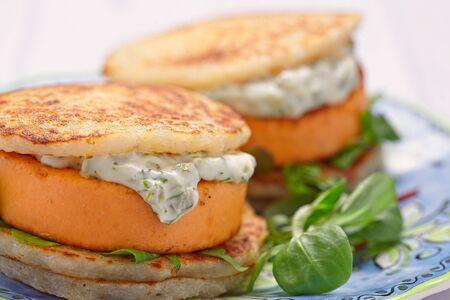 Salmon burger with potato pancakes and tartar sauce
