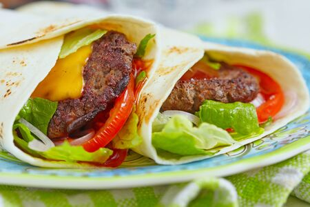 fajita: Fresh tortilla wrap with grilled beef burger and vegetables