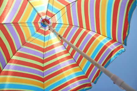 pool party: colorful stripes beach umbrella on blue sky