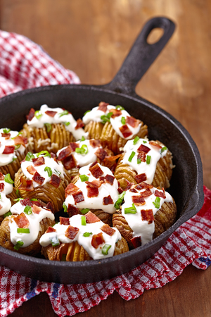 baked potato: Hasselback potatoes with cheese, sour cream, bacon and green onion Stock Photo