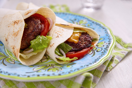 tortilla wrap: Fresh tortilla wrap with grilled beef burger and vegetables