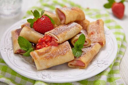 Fresh Strawberry Crepes Rolls with Mint for Breakfast photo