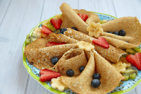 children breakfast: Funny butterfly shaped crepes with berries for kids