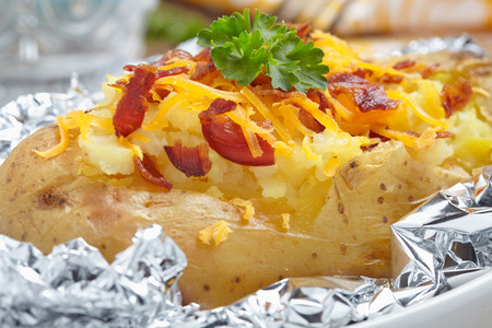 baked potato: Baked potato with bacon, cheese, sour cream and onion Stock Photo