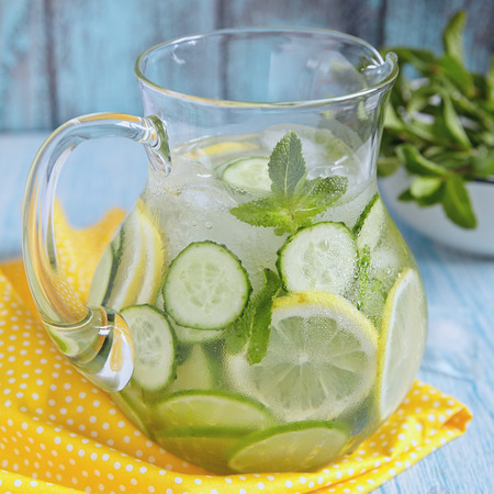 lemon slices: Fruit water with lemon, lime, cucumber and mint in glass pitcher Stock Photo
