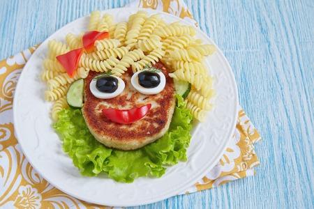 caras graciosas: Funny Girl Face Food con chuleta, Pasta y Verduras Foto de archivo