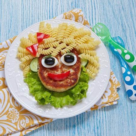 pastas: Funny Girl Face Food con chuleta, Pasta y Verduras Foto de archivo