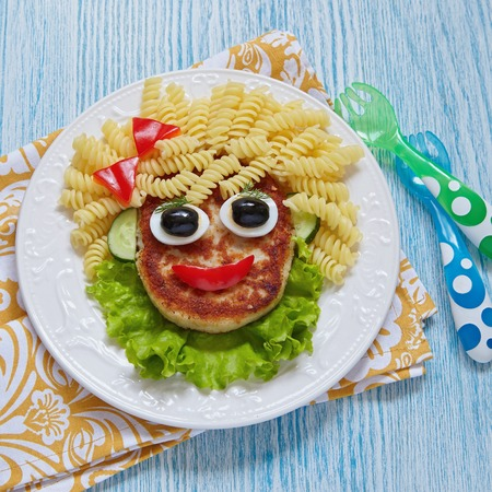 eating pasta: Funny Girl Food Face with Cutlet, Pasta and Vegetables