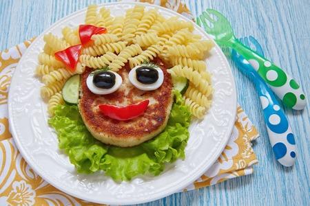 ni�os desayuno: Funny Girl Face Food con chuleta, Pasta y Verduras Foto de archivo