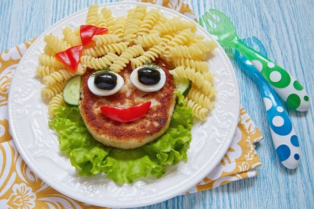 kids eating healthy: Funny Girl Food Face with Cutlet, Pasta and Vegetables