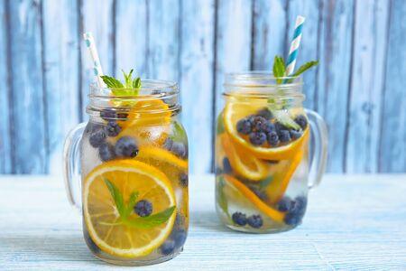 orange water: Orange Blueberry Detox Water on wooden table Stock Photo