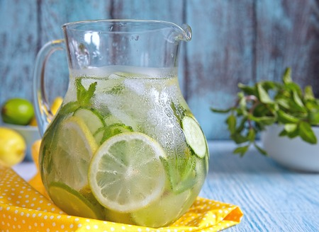 lemon water: Fruit water with lemon, lime, cucumber and mint in glass pitcher Stock Photo