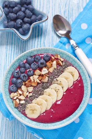 fruit drinks: Breakfast berry smoothie bowl topped with blueberry,almond, banana and chia seeds Stock Photo
