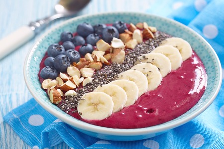 Breakfast berry smoothie bowl topped with blueberry,almond, banana and chia seeds Stock Photo