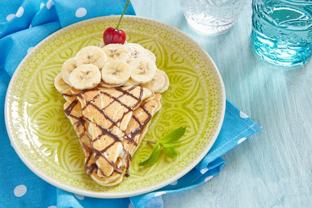 Kids breakfast pancakes with banana and cherry