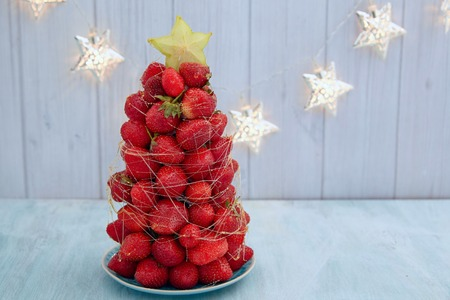 festive background: Strawberry Christmas tree with star fruit and caramel