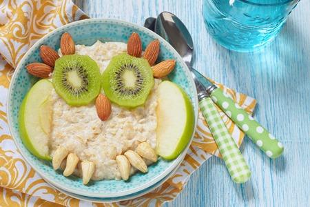 petit dejeuner: Enfants petit-déjeuner du porridge avec fruits et noix