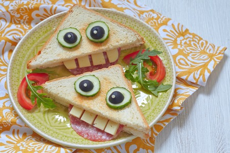 comiendo pan: Sándwich divertido para el almuerzo los niños en una mesa Foto de archivo