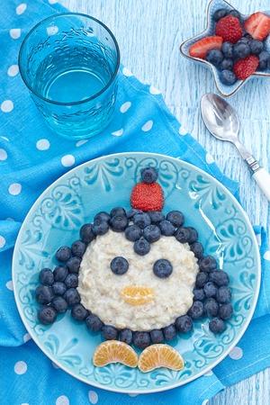 aliments droles: Dr�le petit-d�jeuner pour les enfants de la bouillie avec des baies fra�ches Banque d'images