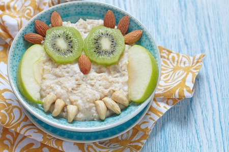 comiendo cereal: Kids breakfast porridge with fruits and nuts