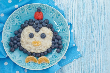 funny people: Funny kids breakfast porridge with fresh berries Stock Photo