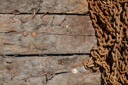 rusty chain: rusty iron chain on a damaged wooden texture background