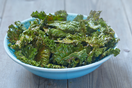 dehydrated: Kale chips with parmesan cheese on wooden table