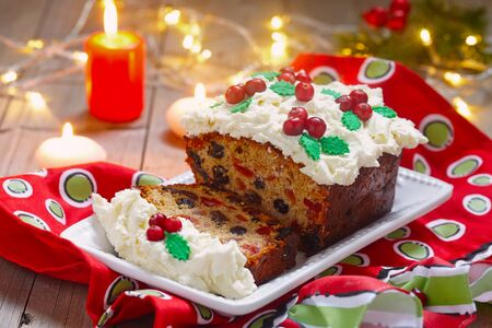 fruitcake: Traditional Christmas Fruitcake with Holly Berry Decoration Stock Photo