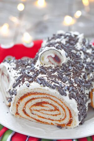 weihnachtskuchen: Fruit yule log cake with chocolate for Christmas