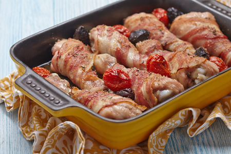 prepared dish: Bacon wrapped chicken legs with tomato and olives