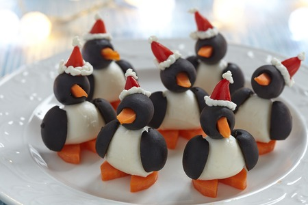 plates of food: olive penguins snack with mozzarella, carrot and pepper santa hat Stock Photo