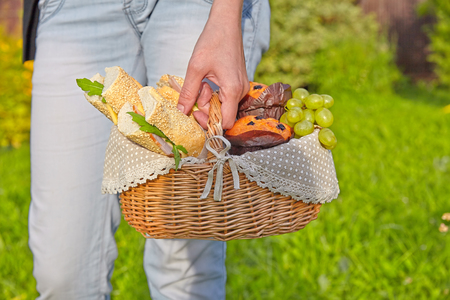 hand basket: Picnic basket with sandwiches, muffins and fruits