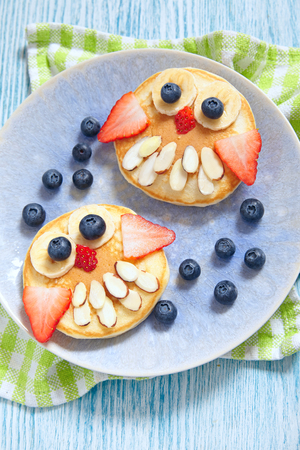 Funny owl pancakes with berries for kids breakfast 스톡 콘텐츠
