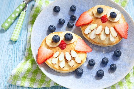 Funny owl pancakes with berries for kids breakfast Standard-Bild