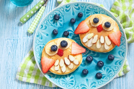 dessert plate: Funny owl pancakes with berries for kids breakfast Stock Photo