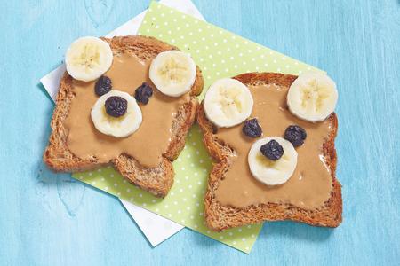 Tenga cachorros hechas de pan integral con mantequilla de maní, plátano y pasas de uva
