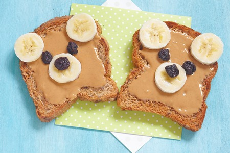 Bear cubs made of whole wheat bread with peanut butter, banana and raisins Reklamní fotografie - 55800327
