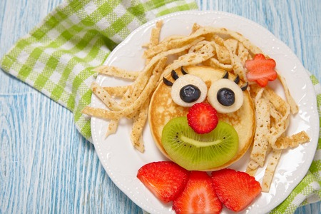 crepes: Funny girl pancake face with fruits and berries Stock Photo
