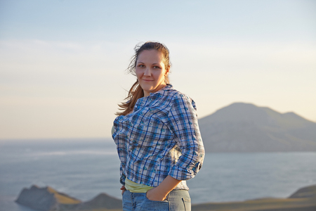 women sitting: Woman traveler looks at the edge of the cliff on the  sea bay of mountains in the background