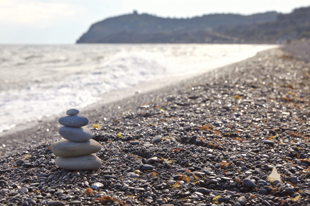 Tiny stone pyramid on a wild pebble beach